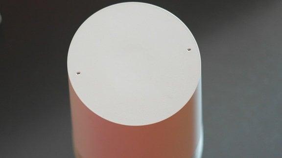 Ein weißes Google Home Gerät ist von oben zu sehen