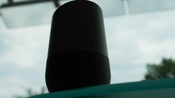 Google Home Gerät steht vor einem großen Fenster.
