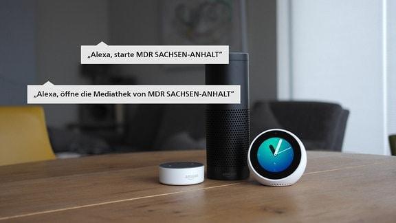 Ein schwarzes Echo 1 Gerät neben einem weißen Echo Spot und einem weißen Echo Dot 2 und von Amazon steht auf einem Tisch in einem Wohnzimmer. Auf dem Bildschirm des Echo Spot ist eine Uhr mit Zeigern zu sehen.