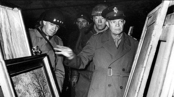 General Dwight David Eisenhower inspiziert mit General Omar Nelson Bradley und General George Smith Patton, jr. die von Nazis gestohlenen Gemälde im Bergwerk Merkers.