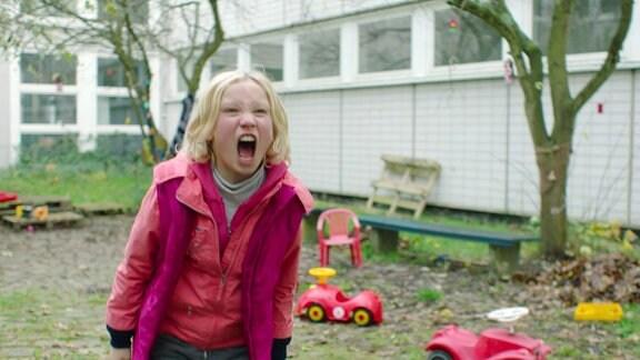 Ein Kind steht auf dem Spielplatz und schreit laut.