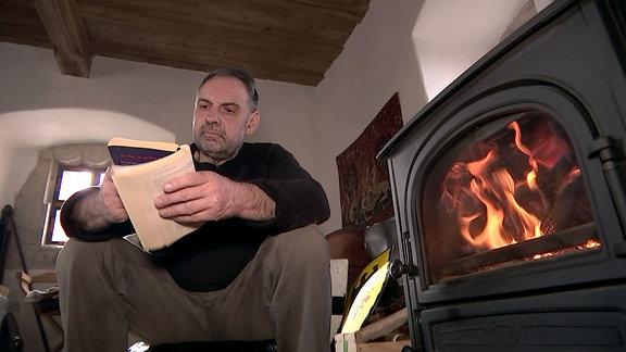 Ein Mann sitzt neben einem Kamin und liest in einem Buch.