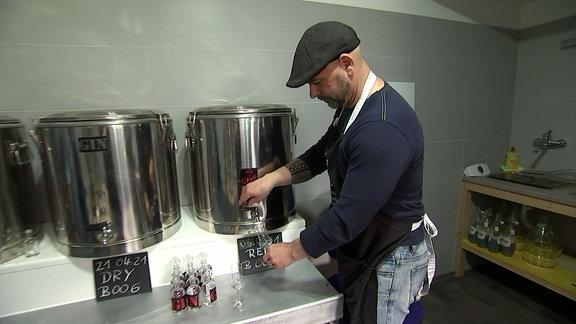 Ein Mann füllt ein Glas mit Gin aus einem Fass ab.