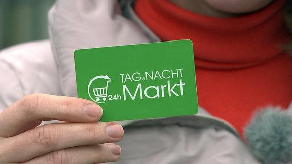 """Eine Hand hält eine Karte mit der Aufschrift """"24h Tag Nacht Markt""""."""