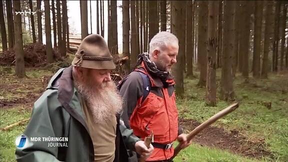 zwei Männer laufen durch einen Wald