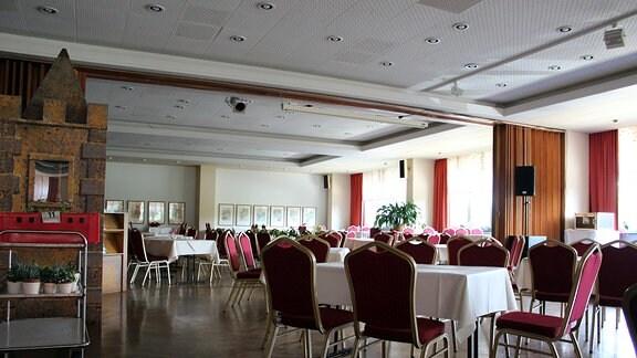 Der moderne Speisesaal eines Hotels mit Roten Stühlen und weißen Tischdecken. Es ist das einstige FDGB-Heim Wurzbach, heute Aparthotel am Rennsteig