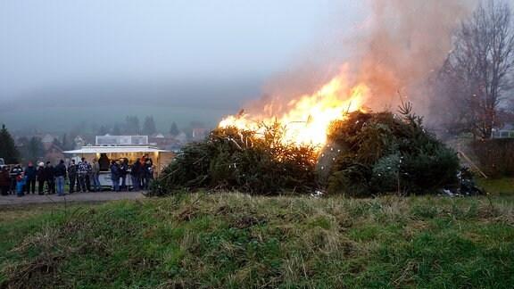 Ein großer Haufen abgeschmückter Weihnachtsbäume brennt. Im Hintergrund stehen Menschen vor einem kleinen Bratwurst-Stand.