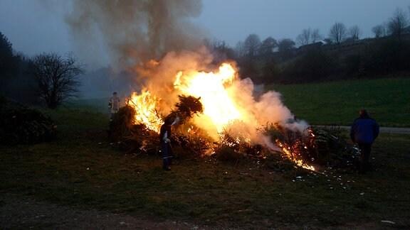 Auf einer Wiese brennt ein großer Haufen Tannenbäume. Ein Mann in Freuerwehruniform wirft eine Tanne ins Feuer.