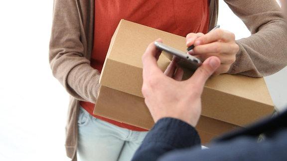 Frau unterzeichnet für Paket an der Haustür