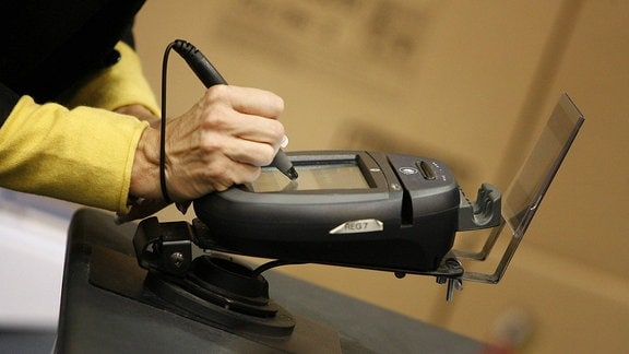 Mann unterschreibt auf dem Display eines Kartenlesegerätes
