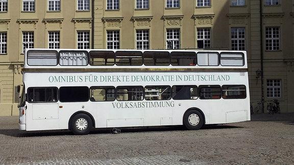 Auf einem Platz steht ein weißer Doppelstockbus mit der Aufschrift Omnibus für direkte Demokratie in Deutschland Volksabstimmung
