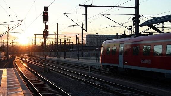 Regionalbahn steht bei Sonnenuntergang am Bahnhof