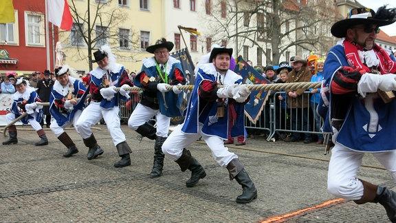 Männer im Kostüm ziehen an einem dicken Seil