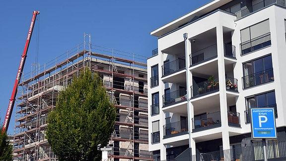 Ein fertiges und ein entstehendes Wohnhaus an einer Wohnungsbaustelle in Erfurt