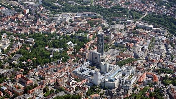 Blick aus der Luft auf das Stadtzentrum von Jena. Aus den Häusern ragt ein Komplex von Hochhäusern heraus. Dabei handelt es sich um den Jentower sowie um das alte Zeiss-Werk