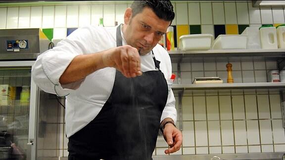 Ein großer, dunkelhaariger Mann mit weißem Oberteil und schwarzer Kochschürze steht hinter einem Herd einer Großküche und streut mit einer Hand Salz von oben in ein Töpfchen, aus dem Dampf aufsteigt