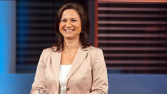 """Die Spitzenkandidatin der Grünen zur Landtagswahl Thüringen, Anja Siegesmund, steht am Pult der MDR-Sendung """"Fakt ist"""". Sie lacht"""