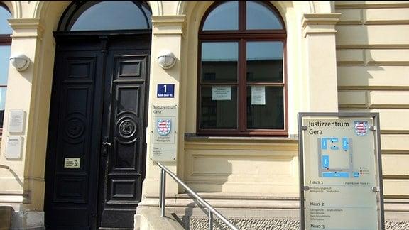 Eingangsbereich des Justizzentrums in Gera. Zu einem gelb gestrichenen Haus aus dem 19. Jahrhundert führt eine Treppe mit mehreren Stufen zu einer dunkelbraunen Holztür hinauf. Beiderseits der Tür sind mehrere Schilder an der Hauswand angebracht. Auf einem der Schilder steht: Justizzentrum Gera