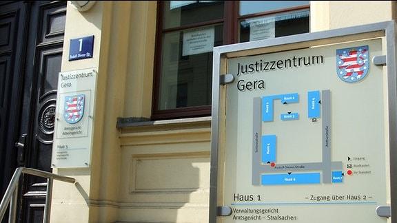 Vor einem gelb gestrichenen Haus steht ein großes Schild mit der Aufschrift Justizzentrum Gera. Unter diesem Schriftzug befindet sich ein Lageplan des Gebäudekomplexes