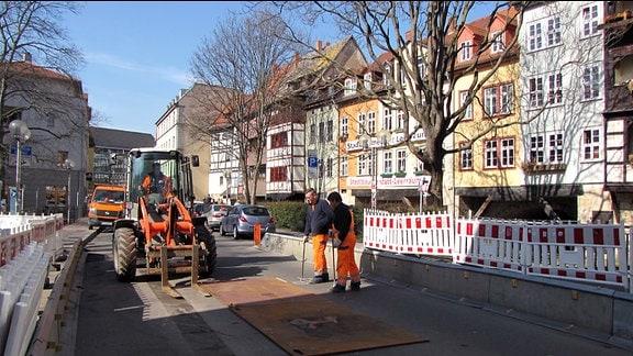 Drei Bauarbeiter verlegen mit Hilfe eines Radladers Stahlplatten auf einer Brücke.