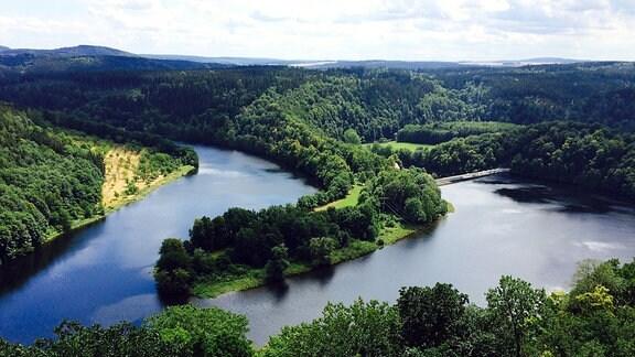 Blick von oben auf einen Fluss und eine Staumauer