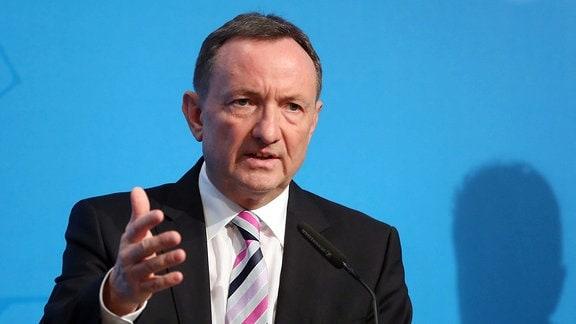 Ein Mann in Anzug und Krawatte steht an einem Pult und spricht in ein Mikrofon. Er macht mit der rechten Hand eine Bewegung.