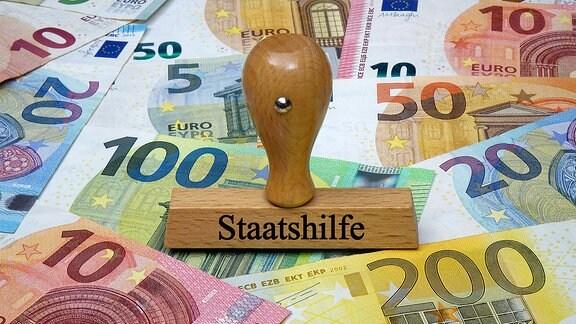 Geldscheine und Stempel mit dem Aufdruck Staatshilfe