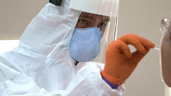 Einh Mann in Schutzkleidung nimmt von einem Patienten einen Abstrich