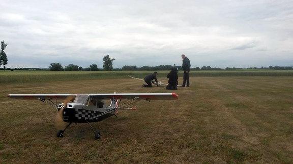 Drei Männer basteln an einem Modell-Segelflugzeug, während ein anderes gerade abhebt