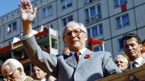 Der DDR-Partei- und Staatschef Erich Honecker  winkt am 1. Mai 1986 von einer Ehrentribühne in der Berliner Karl-Marx-Allee, links Willi Stoph.