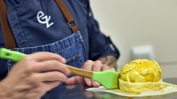 Ein Koch, Eyck Zimmer, pinselt ein Blätterteig-Küchlein mit Eigelb ein
