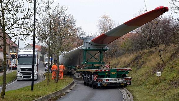 Ein Schwertransporter mit grünem Führerhaus steht in einer leichten Kurve vor einem rötlichen Fachwerkhaus. Auf dem Anhänger liegt ein großes weißes Rotorblatt eines Windrades