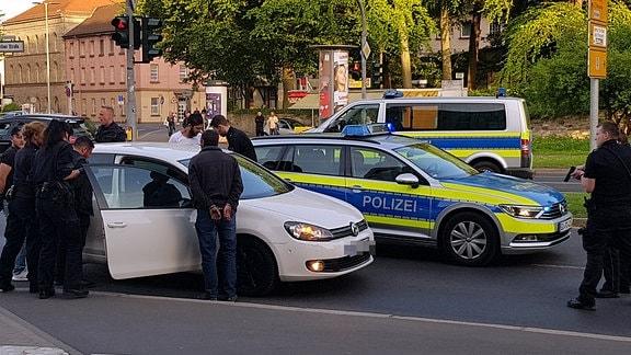 Festnahmen in Göttingen: Mehrere Polizisten stehen um einen weißen PKW herum. Zwei Personen tragen Handschellen. Ein Polizist hält seine Waffe in den Händen. Im Hintergrund sind zwei Polizei-Autos zu sehen