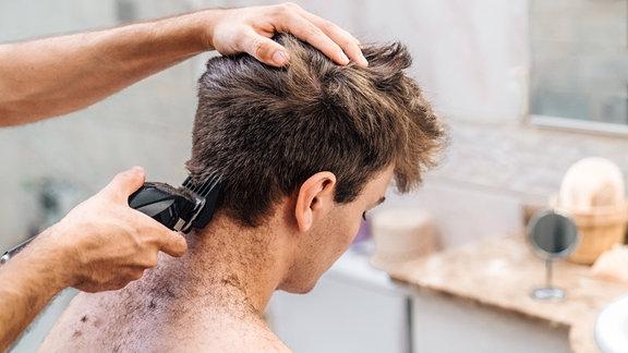 Einen jungen Mann werden die Haare geschnitten