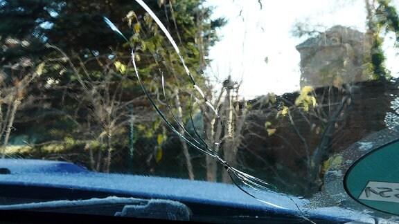 Frontscheibe eines Autos nach der Begegnung mit Eisplatten von einem Lkw