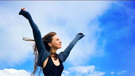 eine glückliche Frau streckt ihre Arme in den Himmel