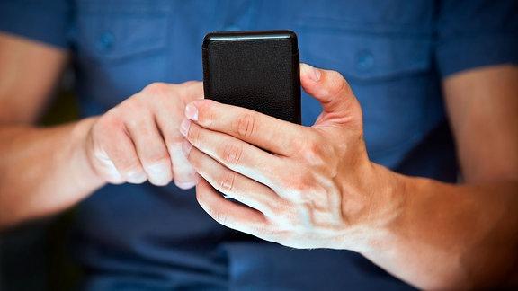 Mann hält Handy und wählt