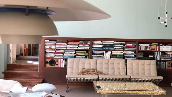 Blick auf das heutige Wohnzimmer des Paares Auerbach/Fischer. Es ist eine Sitzgruppe zu sehen. Dahinter ein Bücherregal, das die Länge der Wand einnimmt.