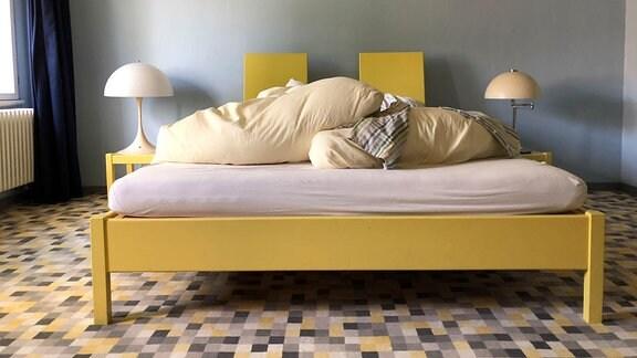 Blick in das Schlafzimmer. Es ist ein Bett zu sehen flankiert von zwei Nachttischen.
