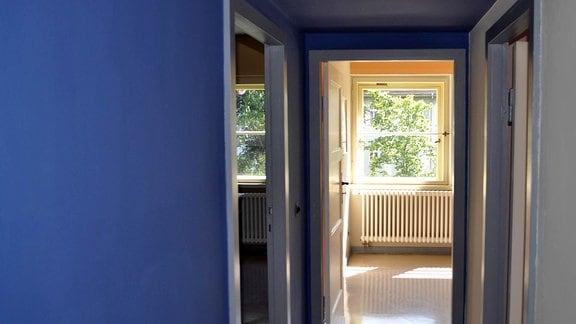 Blick in den blauen Flur. Am Ende des Ganges ist eine Tür geöffnet und Tageslicht erhellt ein gelbgestrichenes Zimmer.