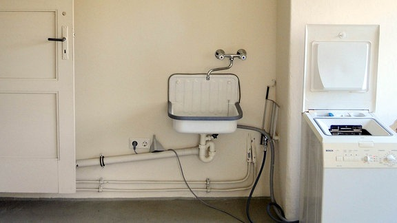 Ausschnitt der Waschküche. Es sind eine Waschmine und ein Waschbecken zu sehen.