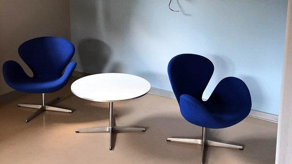 In der Ecke des Herrenzimmer stehen ein Tisch und zwei Stühle.