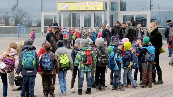 Mehrere Kindergruppen vor einer Glasfassade.