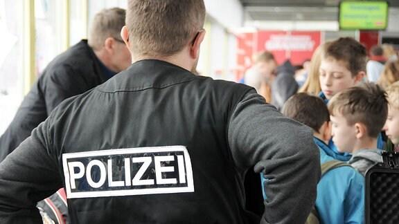 Ein Mann in Polizeiuniform steht vor mehreren Kindern.