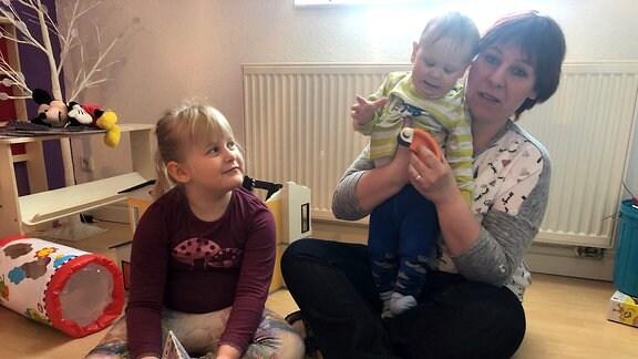 Eine Mutter mit zwei kleinen Kindern