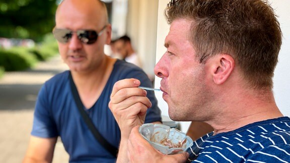 MDR THÜRINGEN-Moderator Marko Ramm isst mit einem Plastiklöffelchen Eis aus einer blauen Plastikschale