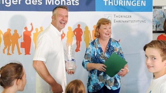 """Vor einem Banner auf dem """"Thüringer des Monats - MDR THÜRINGEN"""" steht, stehen drei Kinder und zwei Erwachsene. Links steht Thüringer des Monats-Gewinner im August Bernd Lehmann. Daneben steht eine Frau. Beide lachen."""