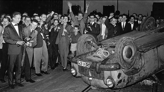 Jugendliche Demonstanten hinter einem umgestürzten Autowrack in der Kochstraße am frühen Morgen des 20.08.1962.