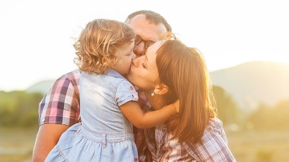 Eltern küssen ihr Kind