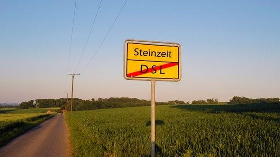 Orsteingangsschild 'Steinzeit' und Ortsausgangsschlid 'DSL' auf einer Landstraße